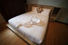 Relaxation bedroom. White towel in swan shape on white bed in relaxation bedroom Stock Photos
