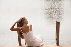 Relaxation belle jeune fille se reposant sur le lac photo stock