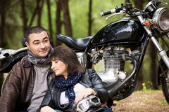 Relaxation after bikers tour. Attractive women sleeping on shoulders of her husband, sitting near bike, relaxation after bikers tour in the forest, active and Stock Images