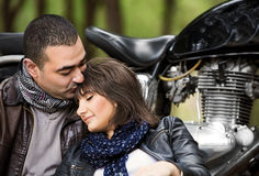 Relaxation after bikers tour. Attractive women sleeping on shoulders of her husband, sitting near bike, relaxation after bikers tour in the forest, active and Stock Image