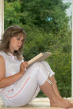 Relaxation with book. The woman sits on a window sill and reads the book Royalty Free Stock Photos