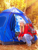 Relaxation in the camp. Happy young traveler relaxing in the camp in bright sunny autumn day, discovering nature, expedition in the forest, active lifestyle royalty free stock photography