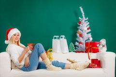 Santa christmas woman relaxing on sofa. Relaxation during Christmas concept. Blonde young woman in Santa hat sitting on sofa relaxing, enjoying leisure time Royalty Free Stock Photography