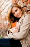 Relaxation in the city, beautiful girl near brick wall Stock Images