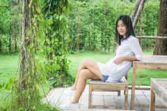 Relaxation Concept : Asian woman relax and smiling on wooden chair at outdoor garden with green natural background. Stock Photos