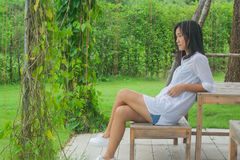 Relaxation Concept : Asian woman sitting on wooden chair at outdoor garden. She relaxing and looking forward with green natural background Royalty Free Stock Photo