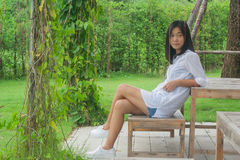 Relaxation Concept : Asian woman sitting on wooden chair at outdoor garden. She relaxing and looking at something with green natural background Stock Photo