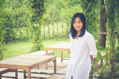 Relaxation Concept : Asian woman wear white shirt standing on grass at outdoor garden and smiling with relaxing. Royalty Free Stock Photos