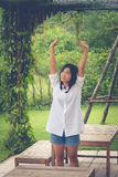 Relaxation Concept : Asian woman wear white shirt and stretch in the garden. Royalty Free Stock Photo