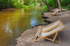 Close up brown wooden bench or armchair on small rocks beside the river with green natural background. Relaxation Concept : Close up brown wooden bench or Royalty Free Stock Image