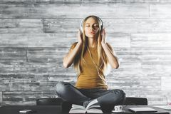 Relaxation concept. Meditating young caucasian woman listening to music through headphones while sitting on office desk with coffee cup, laptop and other items royalty free stock photography
