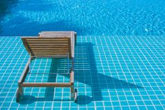 Wooden daybed setting on mosaic tiles in swimming pool at the resort. Royalty Free Stock Images
