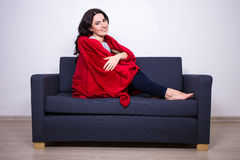 Relaxation concept - young woman sitting on sofa wrapped in red Royalty Free Stock Photography