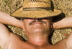Relaxation At Countryside. Smiling Man On A Haystack Royalty Free Stock Photography