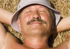 Relaxation At Countryside. Smiling Man On A Haystack Royalty Free Stock Images