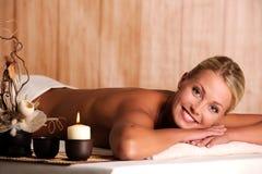 Relaxation de sourire de jeune femme dans le salon de station thermale Images stock