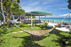 Relaxation environment in tropical beach resort. The hammock is at foreground and the sea coastline is at background. Ko Samet island, Thailand Stock Image