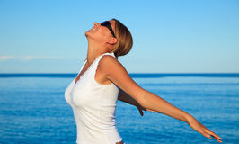 Relaxation exercise on beach. Young Beautiful woman doing relaxation exercises on beach Royalty Free Stock Image