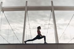 Relaxation exercises. Modern young woman in sports clothing stretching while warming up outdoors stock images