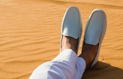 Relaxation. A gentleman`s legs crossed in the desert sand. royalty free stock images