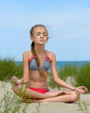 Relaxation. The girl in a pose of a relaxation sits on a sandy beach Stock Images