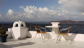 Relaxation on the Island. Table and chairs on lookout terrace on the picturesque volcanic islands. Santorini island, Greece royalty free stock photo