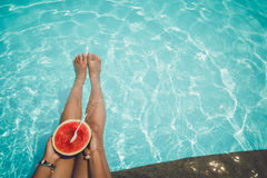 Relaxation and Leisure - Lifestyle in summer of Tanned girl holding watermelon Tropical fruit in the blue pool. Stock Images