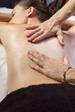 Relaxation. Masseur doing massage on woman body in the spa salon Royalty Free Stock Photos