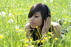 Relaxation on meadow. Teenager when easing with music Royalty Free Stock Photography