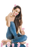Relaxation, meditation. Young beautiful woman sitting on the floor in jeans. The girl holds a rose in hands. Stock Photo