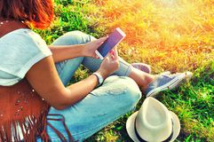 Relaxation with a mobile. Break time. Young woman using cellphone and sitting on the grass wearing jeans, vest of suede leather, white skirt and hat. Sunny Stock Photography