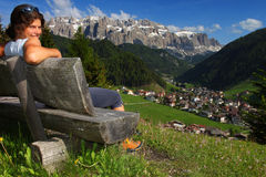 Relaxation in the mountains. Young woman sitting on a bench above summer mountain valley Stock Photo