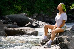 Relaxation on the nature. The girl sits on a stone on the bank of the mountain river Stock Photos