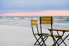 Relaxation place on sandy beach. Beautiful relaxation place on sandy beach. Wooden chairs and table during sunset Stock Image