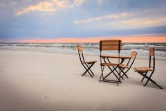 Relaxation place on sandy beach. Beautiful relaxation place on sandy beach. Wooden chairs and table during sunset Royalty Free Stock Photo