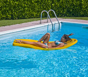 Relaxation pool. Young woman in pool on a floating mattress Stock Photos