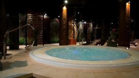 Relaxation pool in spa with waterfall. Empty luxury spa with jacuzzi and swimming pool. Jacuzzi in the sauna. Wellness
