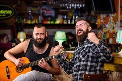 Relaxation in pub. Friends relaxing in pub. Live music concert. Man play guitar in pub. Acoustic performance in pub.  stock images