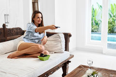 Relaxation. Recreation. Woman Relaxing, Watching TV. Television. Relaxation. Recreation. Portrait Of Beautiful Happy Relaxed Smiling Young Woman Lying On Sofa Stock Photography