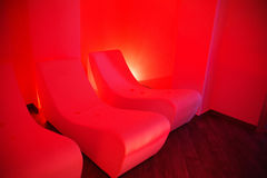 Relaxation room on dark red illumination. Royalty Free Stock Photo