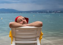 Relaxation at sea. Sad tourist on lounger in sea against backdrop of rain cloud Stock Image