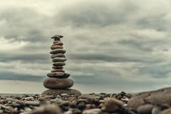 Stone cairn on green blurry background,  pebbles and stones Stock Images