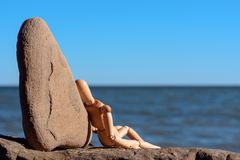 Relaxation at the sea. Wooden dummy sitting on the stony coast Royalty Free Stock Image