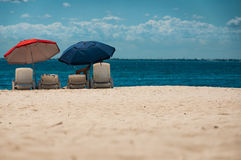 Relaxation in the shade on the beach. A person relaxing under an umbrella on a white sand beach Stock Images