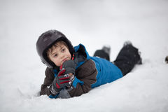 Relaxation after skiing. Portrait of lIttle skier lying on snow with hands on chin Royalty Free Stock Image