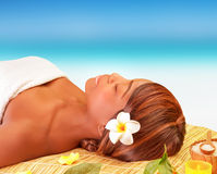 Relaxation on spa resort. Attractive American female sleeping on massage table on the beach, enjoying day spa, luxury summer traveling concept Stock Image