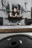 Relaxation before training in gym. Becalmed guy with a beard sits in the squat above a barbell in the gym on the wall with picture background. He holds his hands Stock Photography
