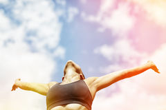 Relaxation under the sun. Woman raised her arms and relaxing Stock Photography