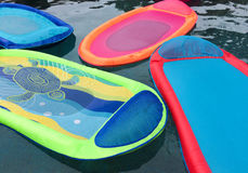 Relaxation and vacation fun. Brightly colored rafts float in a swimming pool Stock Photo