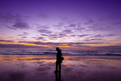 Relaxation walking on the beach at sunset. A silhouette of a woman enjoying ta beautiful purple sunset with silhouette and resting Royalty Free Stock Image
